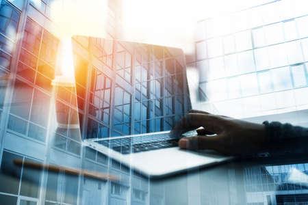 Foto de Businessman works in office with a laptop. Concept of internet sharing. double exposure - Imagen libre de derechos