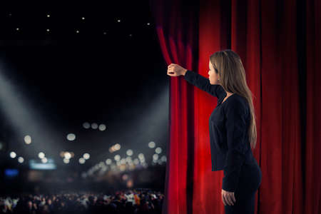 Photo pour Woman open red curtains of the theater stage - image libre de droit
