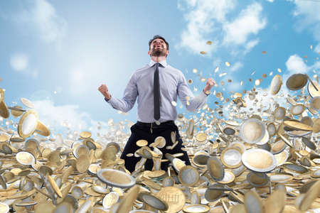 Photo for Businessman exults over a lot of money coins - Royalty Free Image
