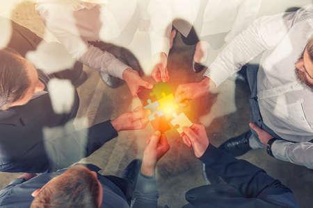 Foto de Business people join puzzle pieces. Concept of teamwork and partnership. double exposure. - Imagen libre de derechos