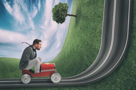 Photo pour Businessman climb an uphill road with a small car. Difficult carrer concept - image libre de droit
