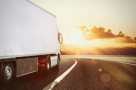 Foto de White truck moving on the road in a natural landscape at sunset - Imagen libre de derechos
