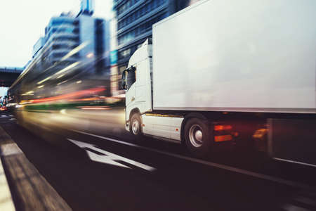 Foto de White truck moving fast on the road in a modern city with light effect - Imagen libre de derechos