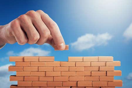 Foto de Businessman puts a brick to build a wall. Concept of new business, partnership, integration and startup - Imagen libre de derechos