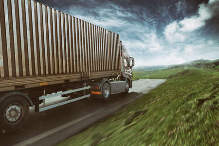 Photo for Grey truck moving fast on the road in a natural landscape with cloudy sky - Royalty Free Image