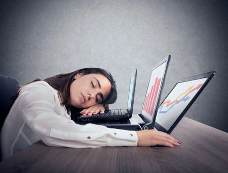 Female worker falls asleep while simultaneously working on three laptops