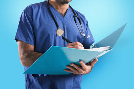 Photo pour Doctor with stethoscope writes on medical record - image libre de droit