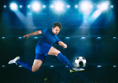 Photo pour Soccer striker hits the ball with an acrobatic kick in the air at the stadium - image libre de droit