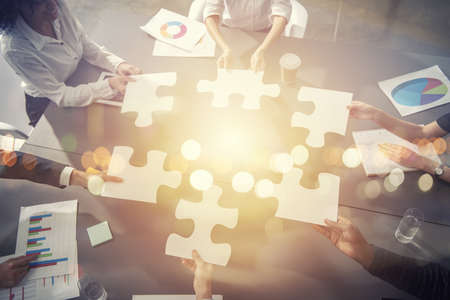 Photo for Business people join puzzle pieces in office. - Royalty Free Image