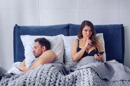 Photo pour Girlfriend secretly chatting with others while he sleeps. Infidelity concept - image libre de droit