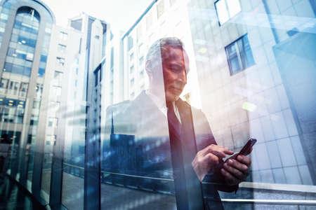 Photo pour Busy senior business man uses mobile phone to communicate - image libre de droit