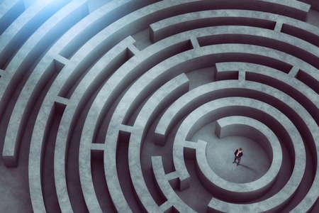 Foto de Confused businessman thinks how to find the right way to exit from a big maze - Imagen libre de derechos