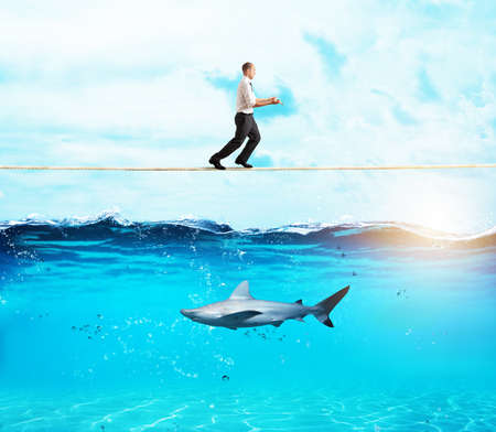 Photo pour Worry man in balance walking on a rope over a shark - image libre de droit