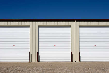 storage units, three numbered units against blue sky