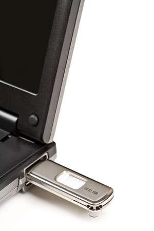 USB memory key plugged into laptop, isolated on white