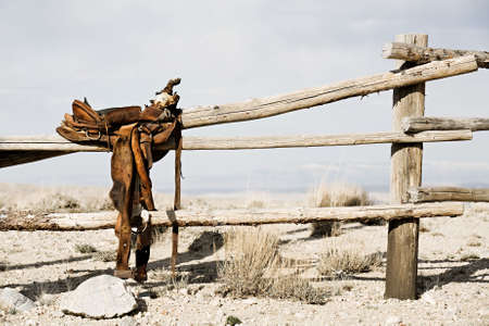 ranch scene - saddle on rural fence, vintage worn saddle in the dry and barren countryside