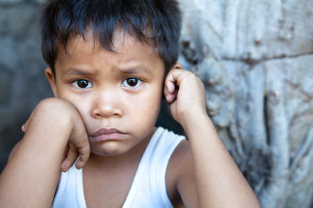 Poverty - portrait of a cute young Asian boy, Filipino male against wall with copyspace.