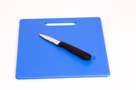A black handled paring knife resting at an angle on a blue cutting board. Isolated on a white background.