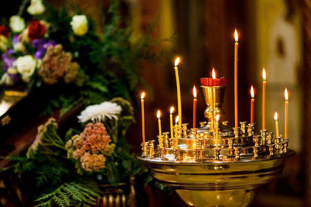 burning candles on the background of icons in the Orthodox Church. Soft focus, selective focus