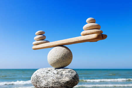 Foto de Symbolic scales of stones on the background of the sea and blue sky. Concept of harmony and balance. Pros and cons concept - Imagen libre de derechos