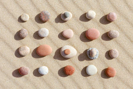 Pattern of colored pebbles on clean sand. The concept of peace. Flat lay, top view
