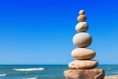 Foto de Rock zen pyramid of white and pink stones on a background of blue sky and sea. Concept of balance, harmony and meditation - Imagen libre de derechos