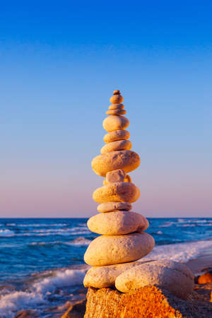 Rock zen pyramid of white stones in the pink rays of the setting sun against the sea Concept of balance, harmony and meditation