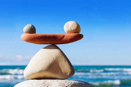 Foto de Concept of harmony and balance. Balance stones against the sea. Rock zen in the form of scales - Imagen libre de derechos