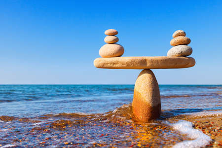 Foto de Symbolic scale of the stones on sea background closeup. Concept of harmony and balance. work-life, emotional balance - Imagen libre de derechos