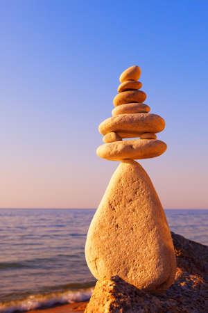 Stones balance on a background of sea sunset. Calm and meditation. Concept of harmony and balance.