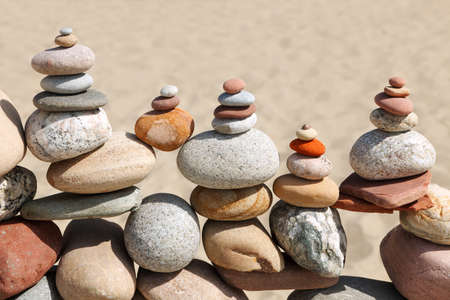 Photo pour Lots of balanced, colorful pebbles on a beach on the background of the sand. Concept of Life balance, harmony and meditation - image libre de droit