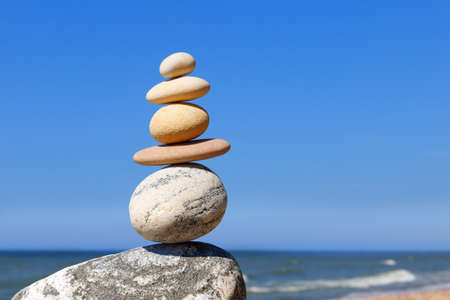 Photo for Rock zen Pyramid of balanced stones against the background of the sea and blue sky. Concept of balance, harmony and meditation - Royalty Free Image