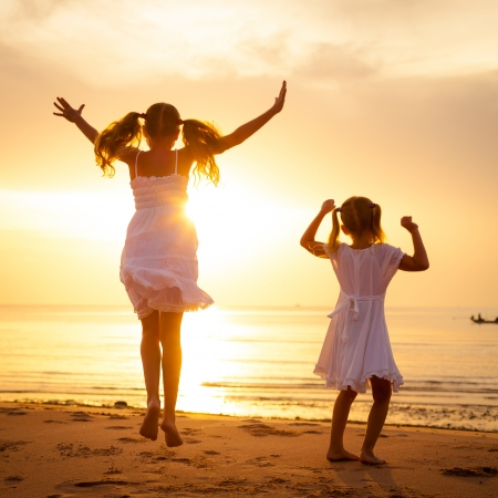 Happy children jumping on the beach on the dawn time