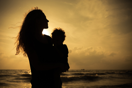 Mother and little son silhouettes on beach at sunset