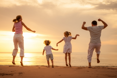 Happy beautiful family dancing on the  beach on the  dawn time