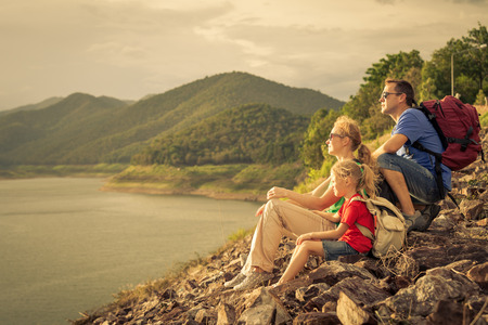 Foto de Happy family sitting near the lake at the day time. Concept of friendly family. - Imagen libre de derechos