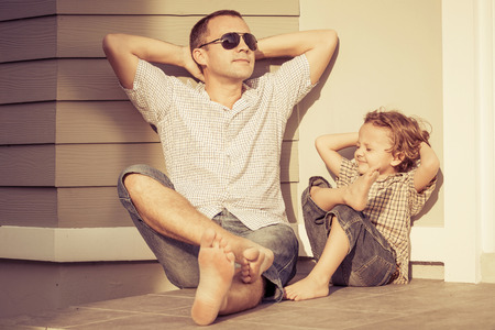 Photo pour Dad and son playing near a house at the day time - image libre de droit