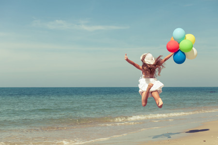 Photo pour Teen girl with balloons jumping on the beach at the day time - image libre de droit