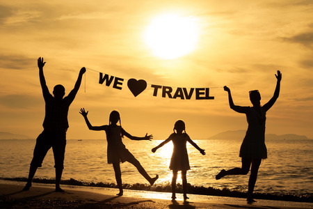 "Happy family standing on the beach at the sunset time. Parents hold in the hands  inscription ""We love travel\"". Concept of friendly family."