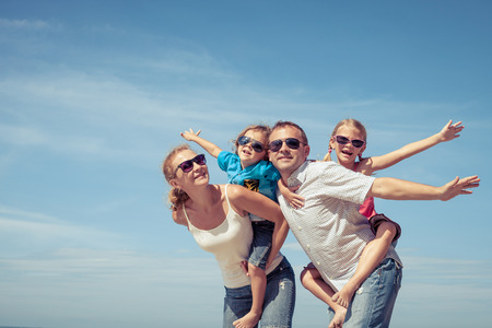 Photo pour Happy family standing on the beach at the day time. Concept of friendly family. - image libre de droit
