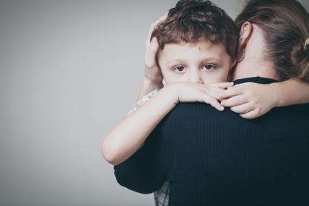 Foto de sad son hugging his mother at home. Concept of couple family is in sorrow. - Imagen libre de derechos
