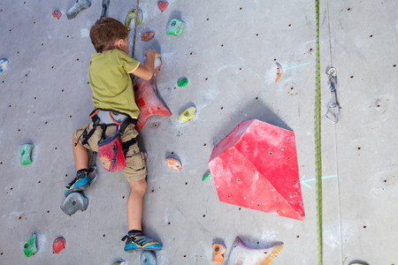 Photo pour little boy climbing a rock wall indoor - image libre de droit