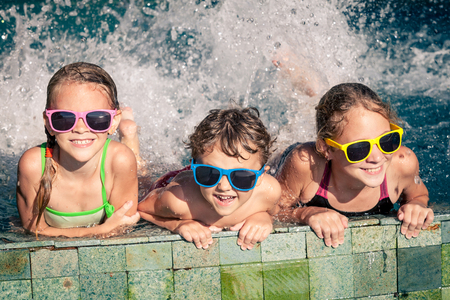 Foto de Three happy children  playing on the swimming pool at the day time. Concept of friendly family. - Imagen libre de derechos