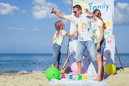 Photo pour Happy father and children playing with paint on the beach at the day time. Concept of friendly family. - image libre de droit