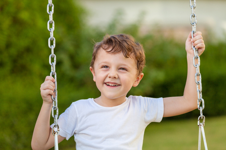 Foto per happy little boy playing on playing on the playground at the day time - Immagine Royalty Free
