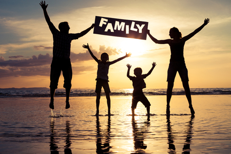 Foto de Happy family jumping on the beach at the sunset time. Parents hold in the hands  inscription Family. Concept of happy family. - Imagen libre de derechos
