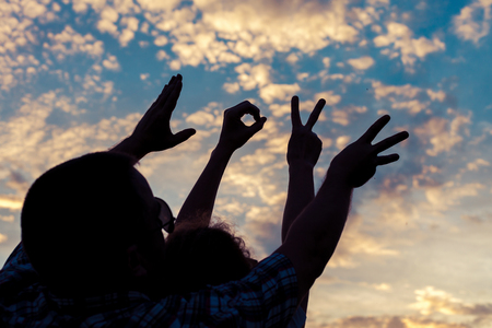 Photo pour Love sign language at the sunset time. Concept of friendly family and of summer vacation. - image libre de droit