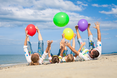 Foto de Happy family playing with balloons on the beach at the day time.  People having fun on the beach. Concept of friendly family and of summer vacation. - Imagen libre de derechos