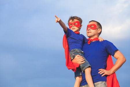 Foto de Father and son playing superhero at the day time. People having fun outdoors. Concept of friendly family. - Imagen libre de derechos