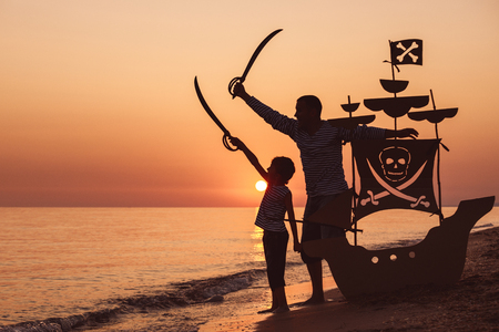 Photo pour Father and son playing on the beach at the sunset time. They playing with a cardboard pirate ship. People having fun outdoors. Concept of summer vacation and friendly family. - image libre de droit